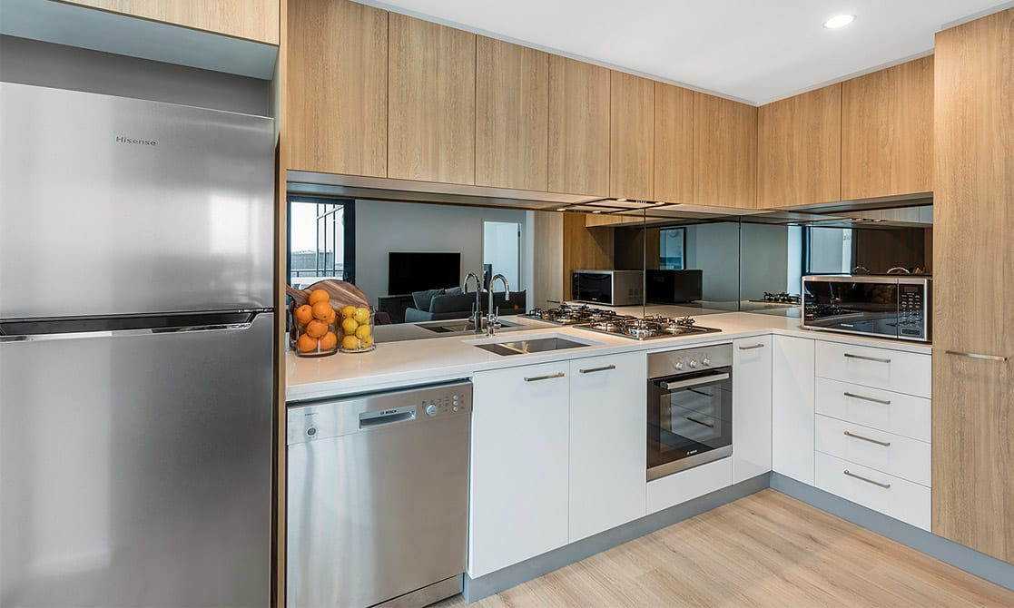 Full modern kitchen equipped with fridge, cook top, over and microwave