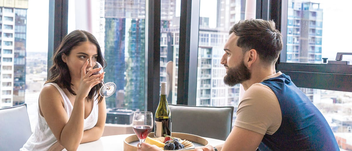 Young couple on romantic holiday enjoying dinner at participating AVANI and Chill hotel