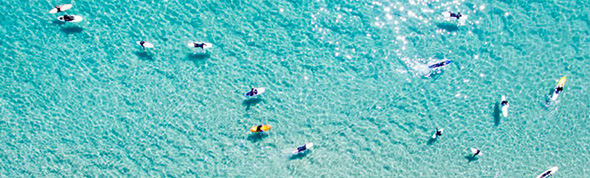 aerial view people surfing near AVANI Broadbeach hotel Gold Coast, Australia