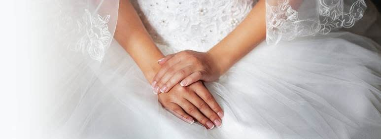 Hands of the bride who is in a wedding dress