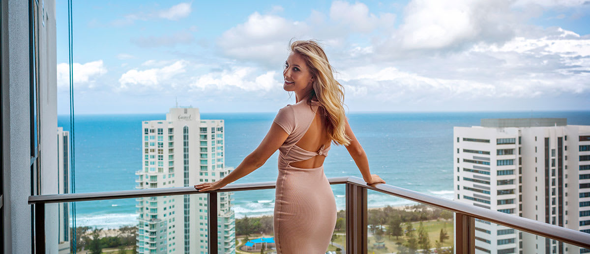 Laura Dundovic looking at Broadbeach and ocean from balcony of AVANI Broadbeach hotel Gold Coast