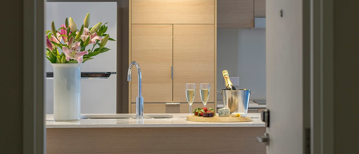 one bedroom suite entry with flower and wine in the kitchen at Avani Broadbeach Gold Coast Queensland