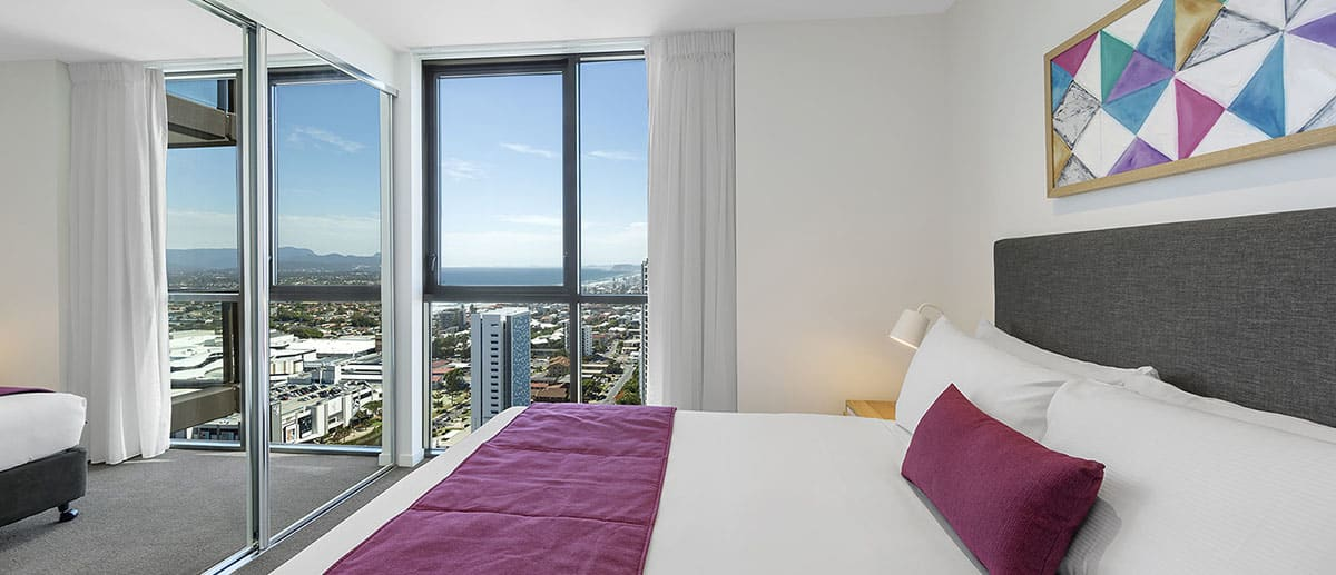 comfy queen-sized bed with city view at one bedroom ocean suite AVANI Broadbeach Gold Coast Hotels