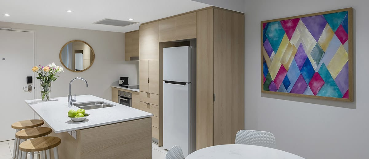 fully equipped kitchen with fridge, oven and stove top and modern painting on the wall of living room at one bedroom ocean suite AVANI Broadbeach Gold Coast Hotels