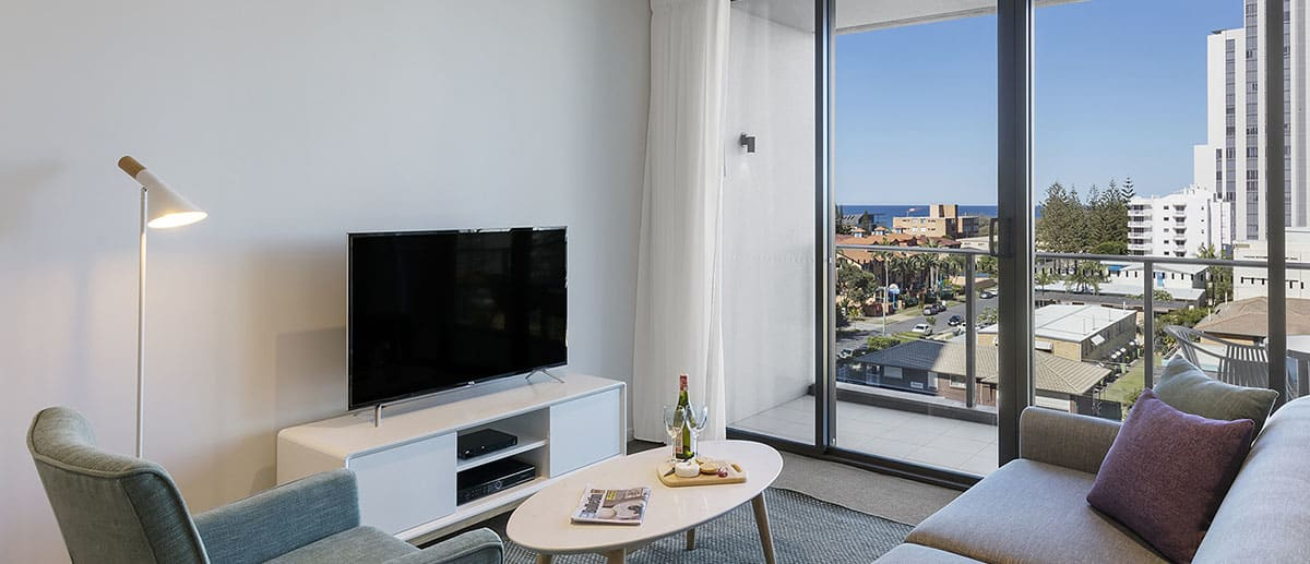 comfortable and spacious living room with ocean view at one bedroom ocean suite AVANI Broadbeach Gold Coast Hotels
