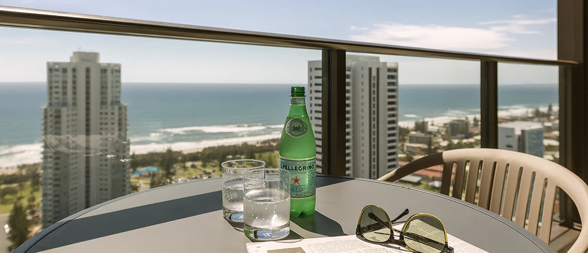 drinks and sun glass on the table of the spacious balcony with grand ocean view at the one bedroom premier ocean suite AVANI Broadbeach Gold Coast Hotels