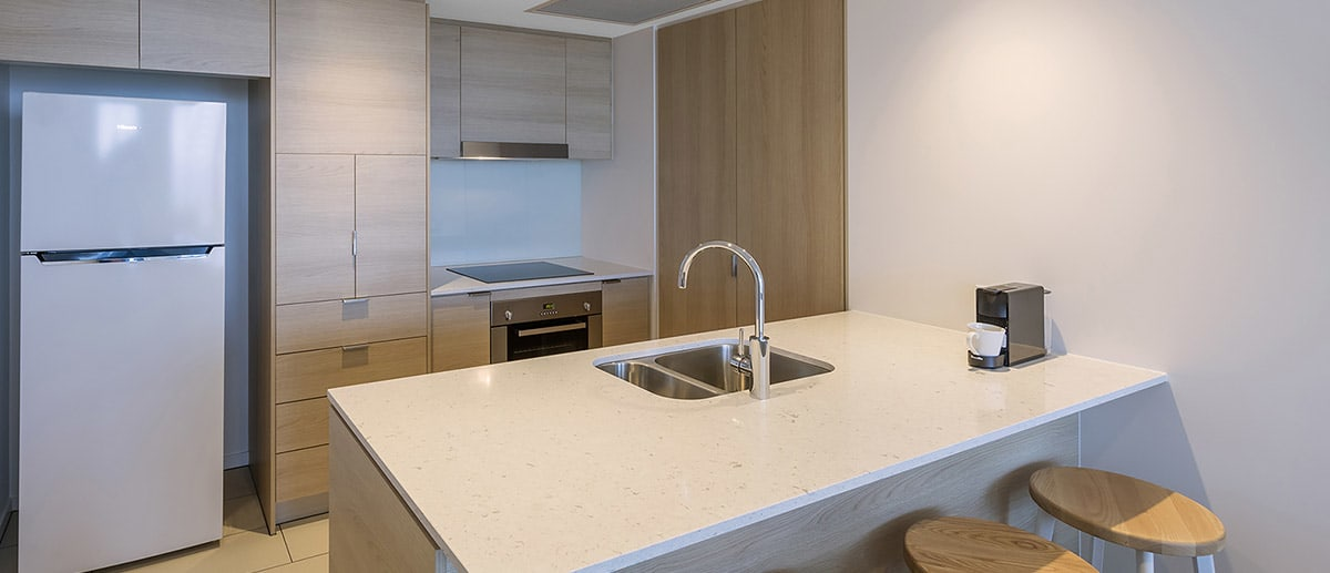 Spacious and well-appointed kitchen with fridge, oven, stove top and dining table provided at the one bedroom premier ocean suite AVANI Broadbeach Gold Coast Hotels