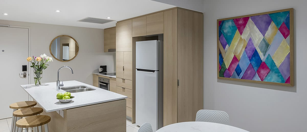 Spacious and well-appointed kitchen with fridge, oven, stove top and separate dining area at the one bedroom premier ocean suite AVANI Broadbeach Gold Coast Hotels