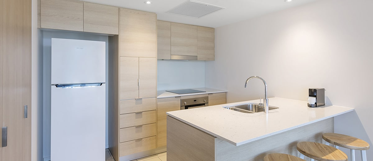fully equipped kitchen with fridge, oven, stove top at one bedroom suite AVANI Broadbeach Gold Coast Hotels