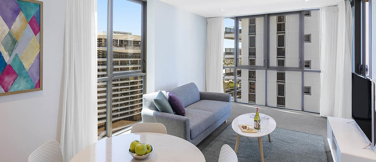 comfortable and spacious dining and living area with city view at one bedroom ocean suite AVANI Broadbeach Gold Coast Hotels