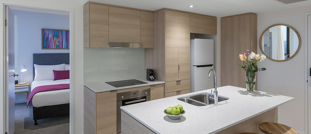 Spacious and well-appointed kitchen with fridge, oven, stove top and dining table provided at the two bedroom ocean suite AVANI Broadbeach Gold Coast Hotels