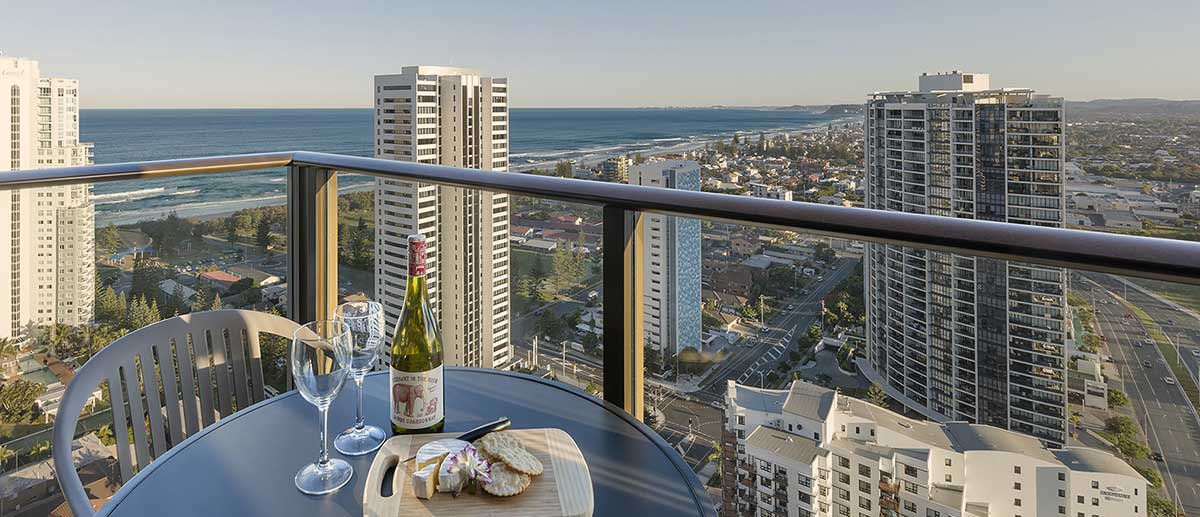 red wine and cheese on the table of the spacious balcony with grand ocean view at the two bedroom ocean suite AVANI Broadbeach Gold Coast Hotels