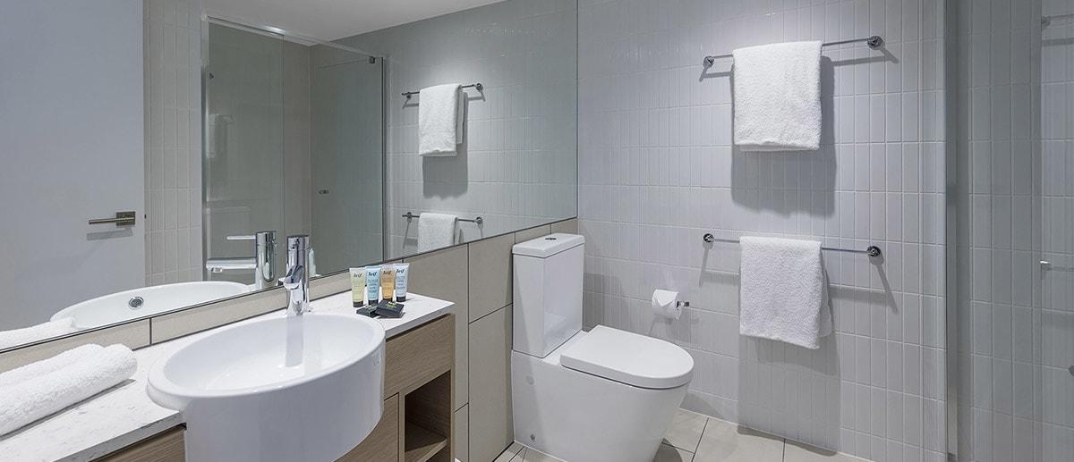 Bathroom with walk-in shower and branded toiletries at two bedroom ocean suite AVANI Broadbeach Gold Coast Hotels