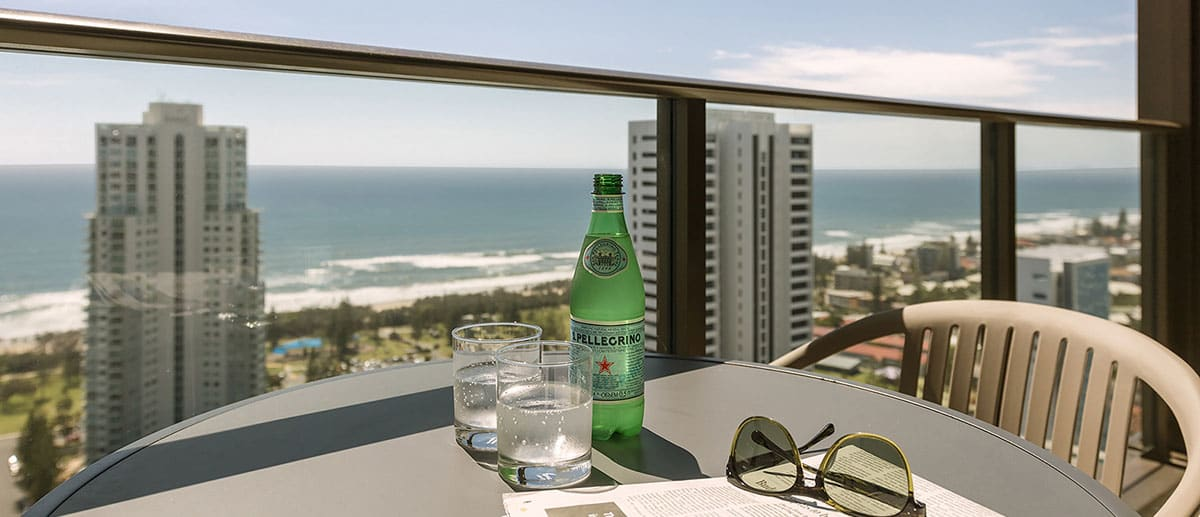 drinks and sunglasses on the table of the spacious private balcony with grand ocean view at the two premier bedroom ocean suite AVANI Broadbeach Gold Coast Hotels