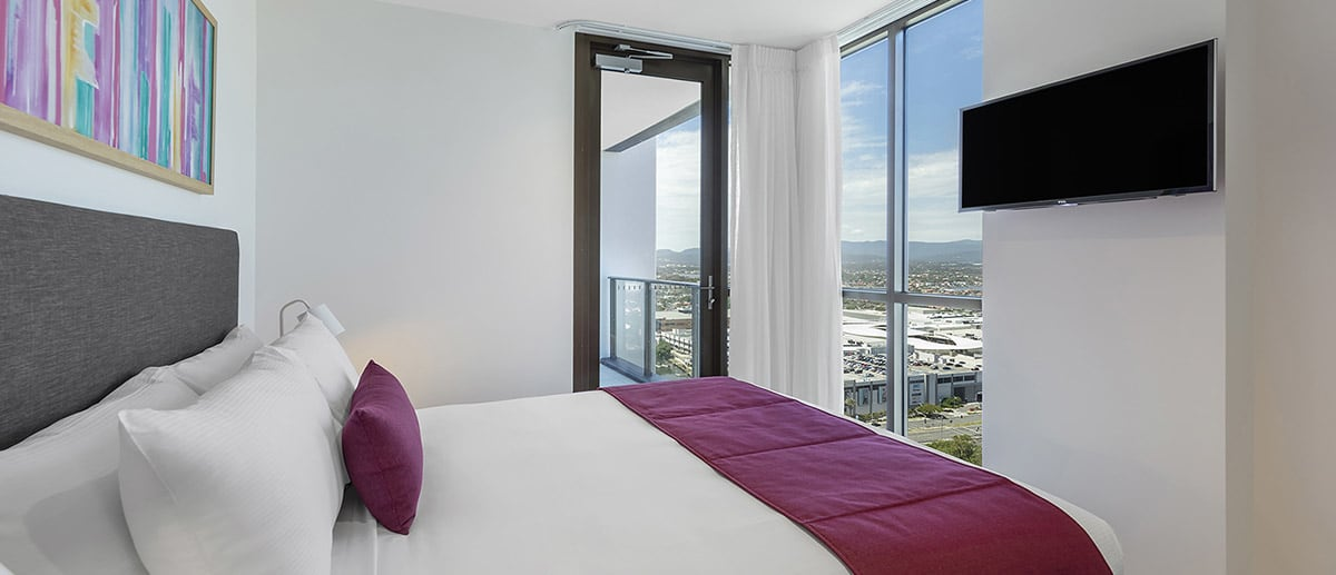 queen sized bed with city view and access to the private balcony at the two bedroom suite AVANI Broadbeach Gold Coast Hotels