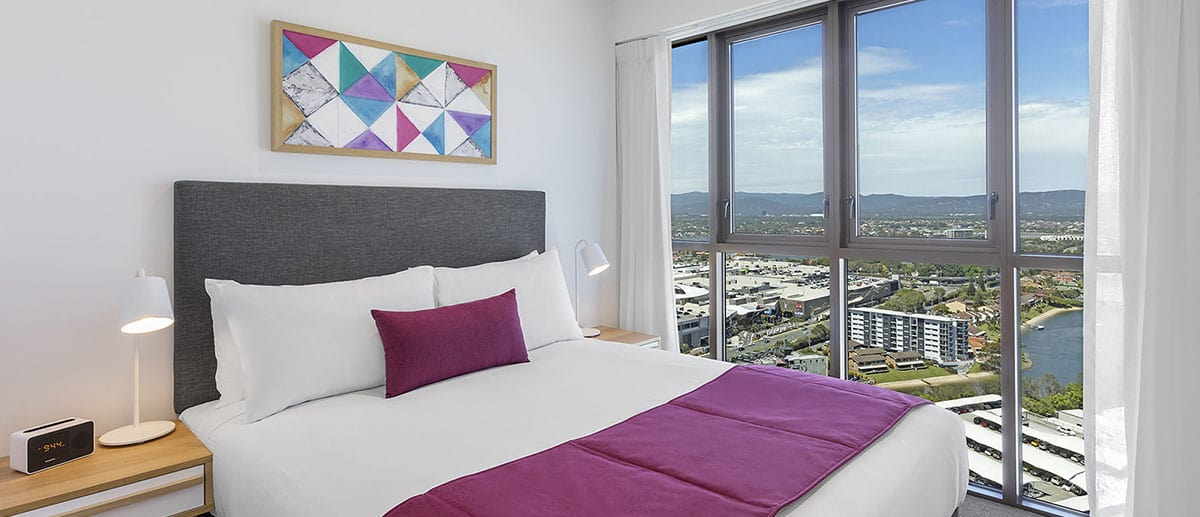 comfortable queen sized bed with city and lake view at the two bedroom suite AVANI Broadbeach Gold Coast Hotels