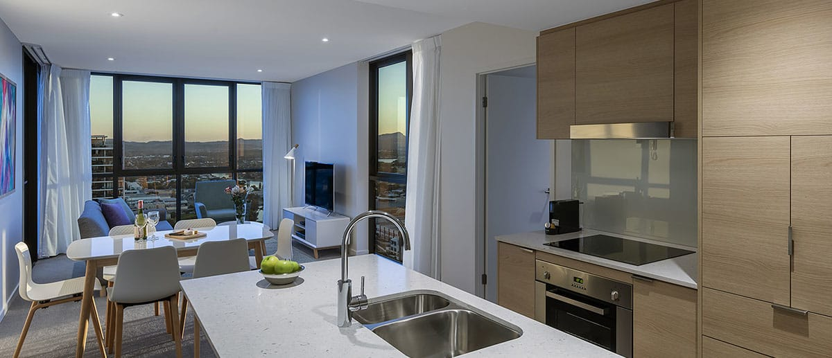 Spacious and separate kitchen, dining and living areas with beautiful city dusk view at the two bedroom suite AVANI Broadbeach Gold Coast Hotels