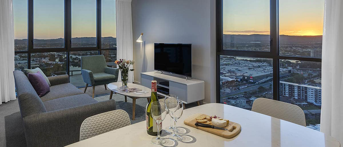 Spacious and separate dining and living areas with beautiful city sunset view at the two bedroom suite AVANI Broadbeach Gold Coast Hotels