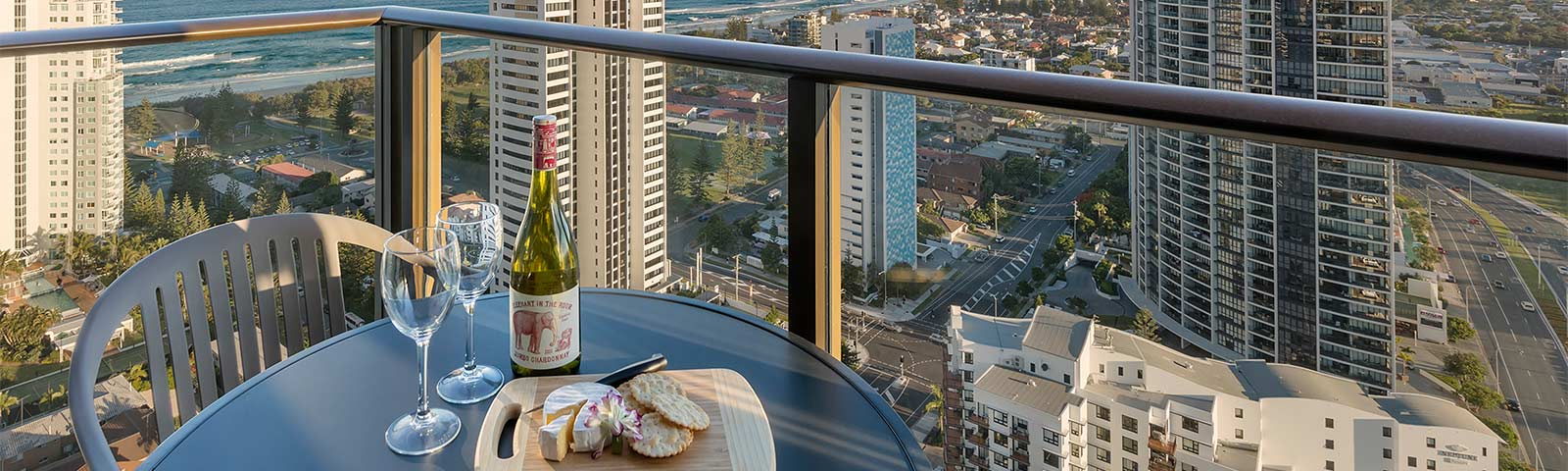 Red wine, two glasses and cheese plate set on the spacious balcony at  two bedroom ocean premier suite of AVANI Broadbeach Gold Coast Residence with breathtaking ocean views and high rise