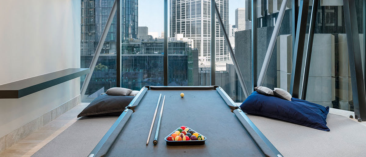 Billiards table near window in games room of AVANI Central Melbourne Hotel with view of CBD outside