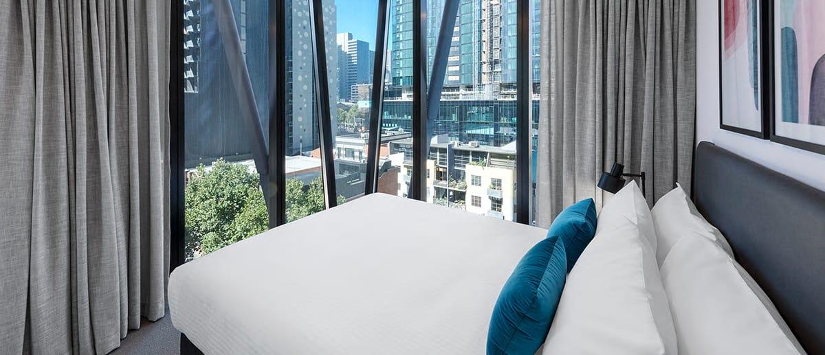 bed 2 bedroom central Melbourne apartment big windows overlooking CBD