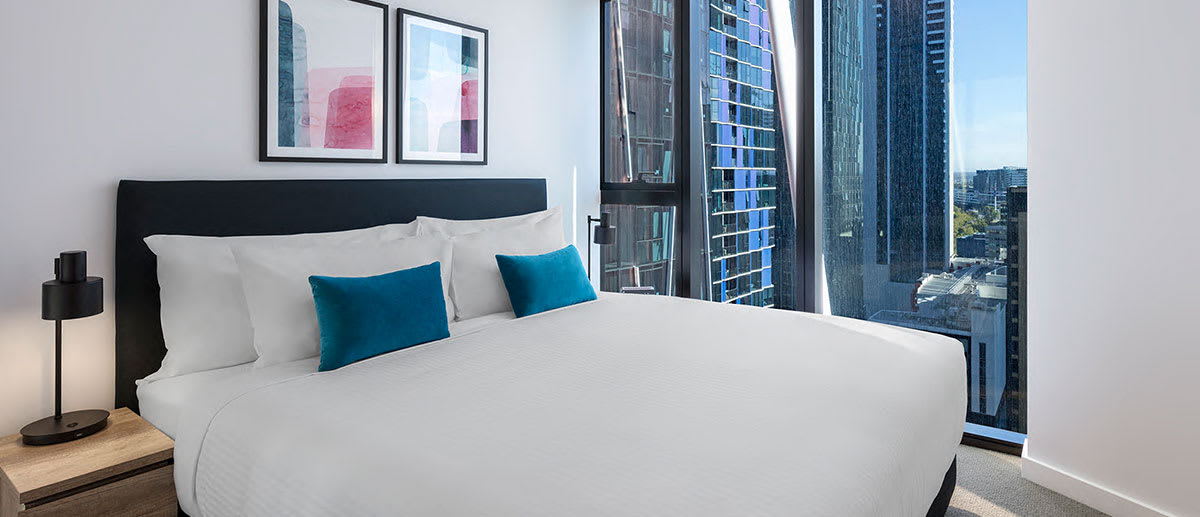 Big queen size bed in 1 Bedroom Apartment in Central Melbourne hotel with large windows and views of city outside