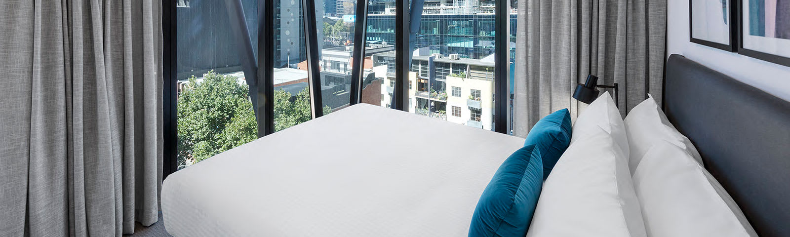 Large hotel bedroom with queen size bed in 2 Bedroom Apartment with big windows overlooking Central Melbourne