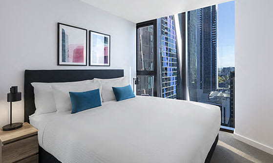 King size bed in 1 Bedroom Apartment of AVANI Central Melbourne hotel with air conditioning