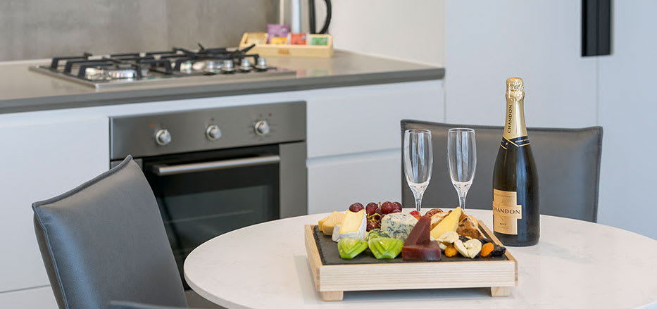 Close up view of champagne grapes and biscuits on table in open plan kitchen of AVANI Central Melbourne hotel room