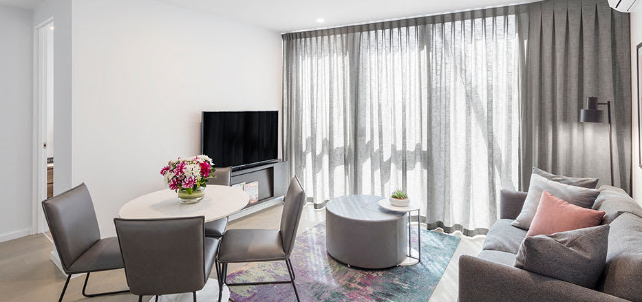 Spacious modern lounge with Foxtel on TV in AVANI Central Melbourne hotel rooms