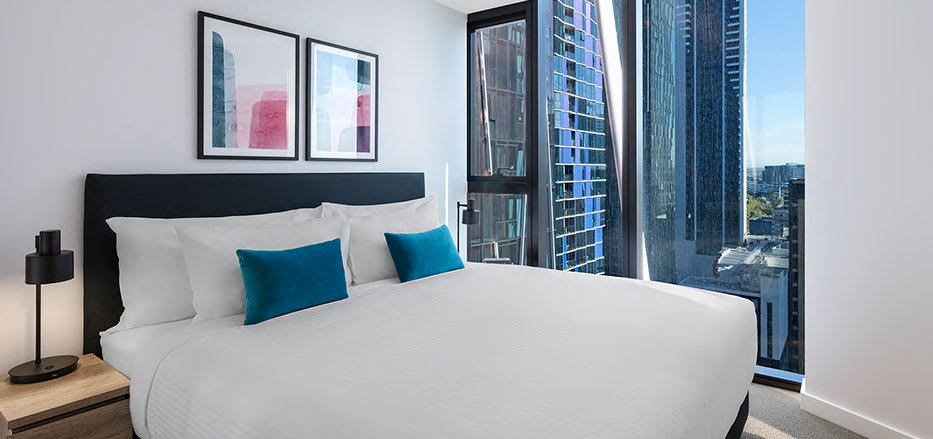 King size bed with best views of Melbourne from AVANI Central Melbourne hotel 1 bedroom apartment