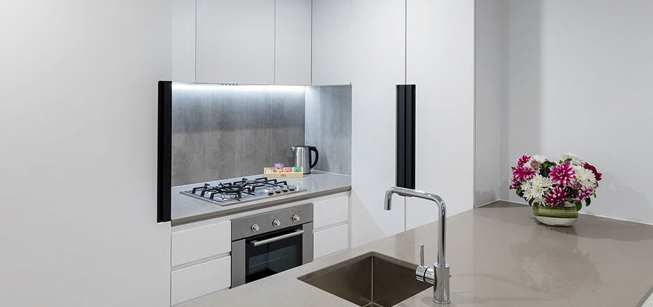 Modern kitchen with big table top in AVANI Central Melbourne 2 Bedroom Apartments