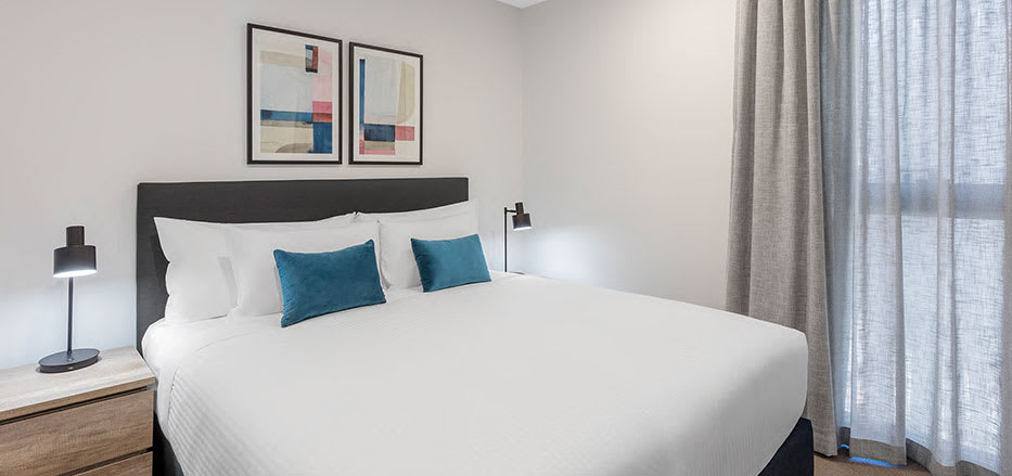 King size bed in air conditioned 2 bedroom suite of AVANI Central Melbourne hotel apartment