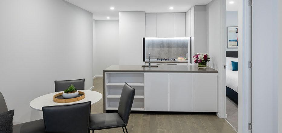 Open plan kitchen and lounge area in 2 bedroom apartment of AVANI Central Melbourne hotel rooms