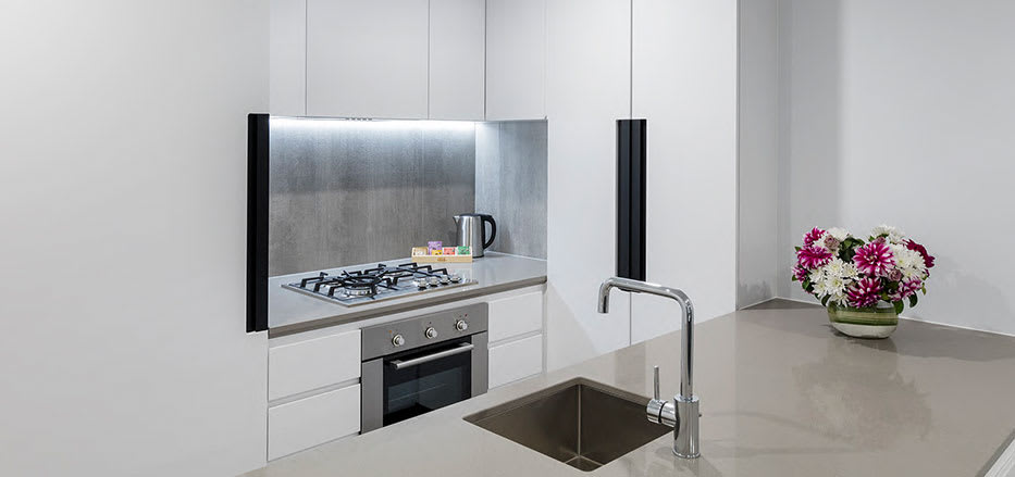 Big clean kitchen with oven and large fridge in AVANI Central Melbourne hotels 2 bedroom apartment