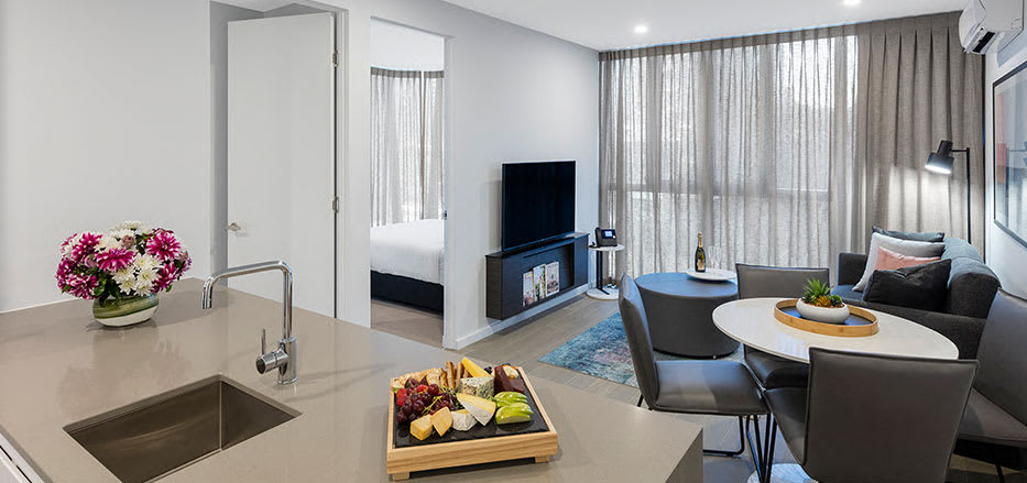 Open plan living area and kitchen in 2 bedroom hotel apartment of AVANI Central Melbourne hotel