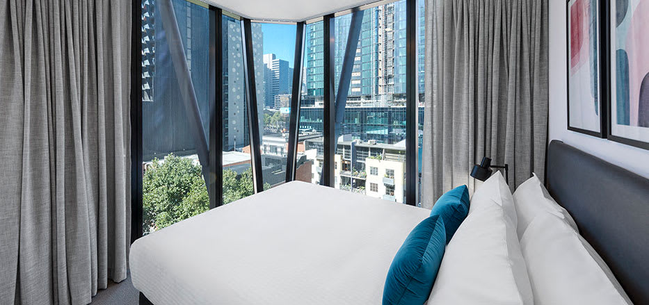 Queen size bed in 2 bedroom apartment overlooking the Melbourne CBD in AVANI Central Melbourne hotel room