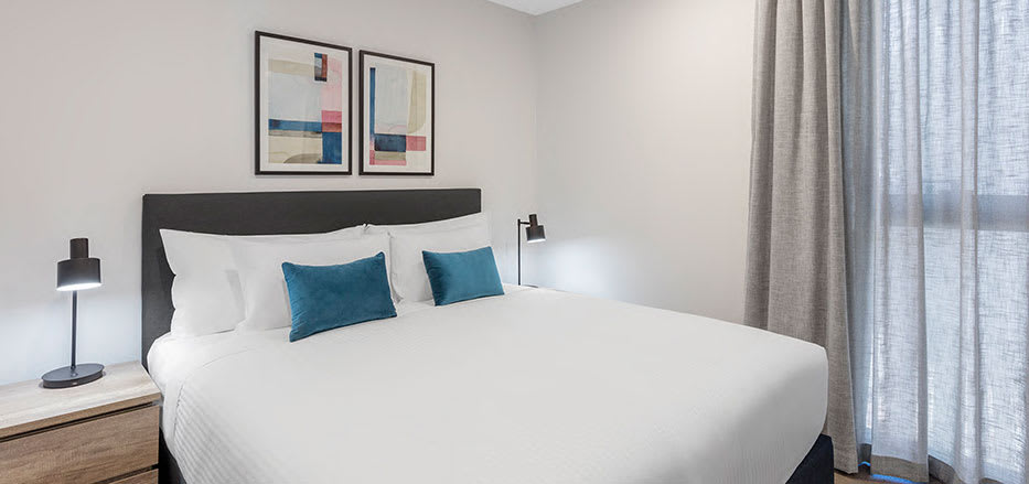 Queen size bed in air conditioned 2 bedroom apartment of AVANI Central Melbourne hotel