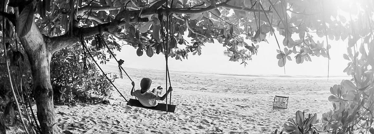 A little boy playing with a swing at the beach