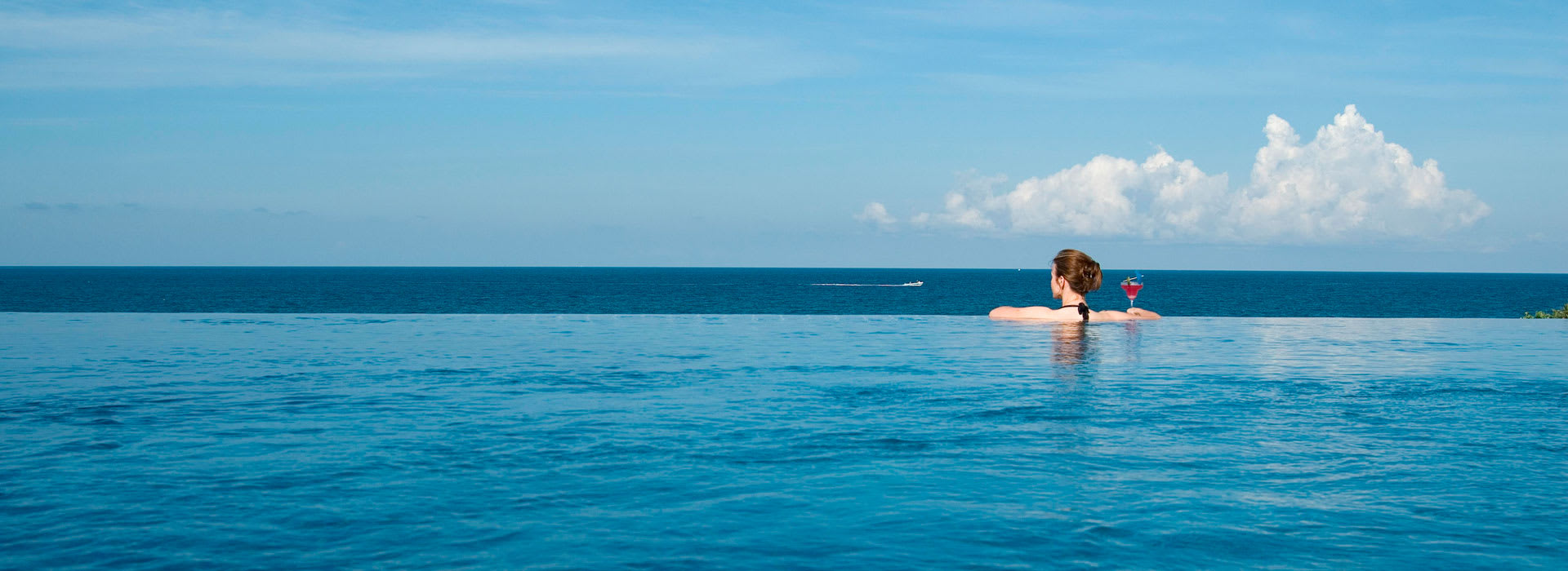 A girl staring at the ocean from the infinity pool