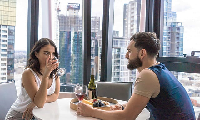 Couple drinking wine at AVANI Central Melbourne apartment hotel with stunning city view