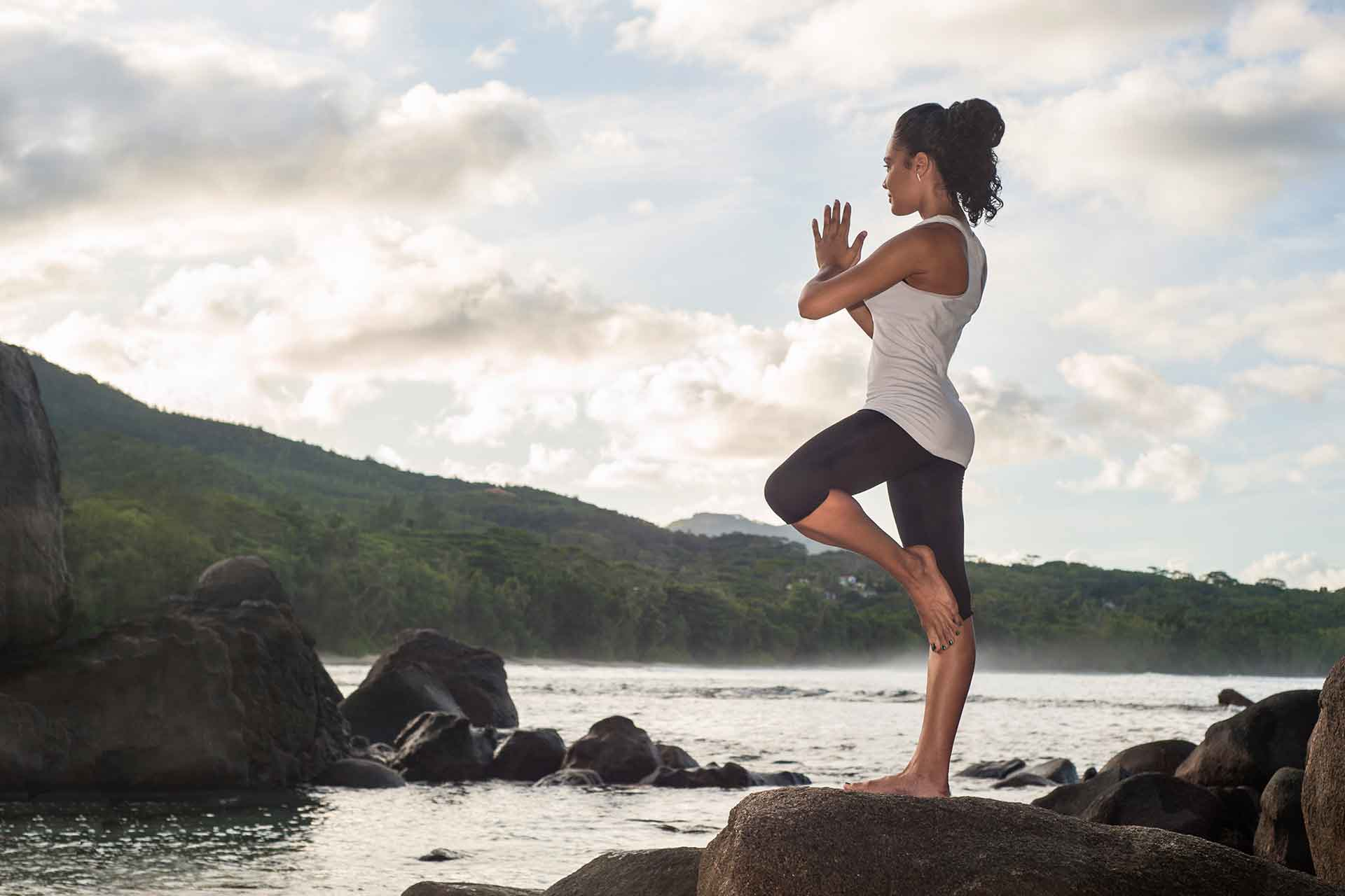 A girl doing yoga on a cliff of Seychelles