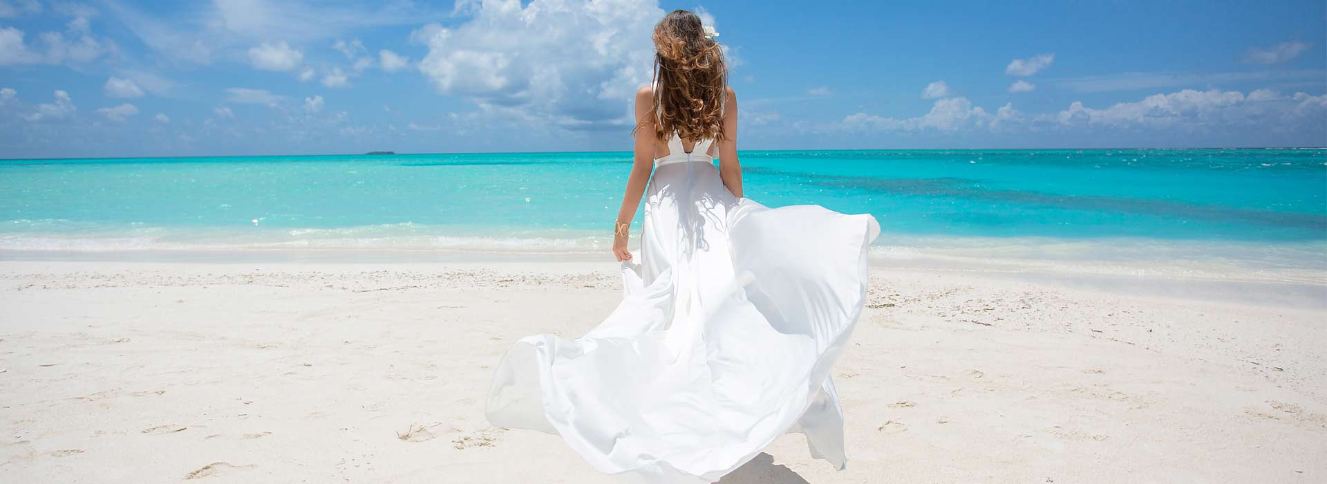 A girl wearing a white frock on the beach