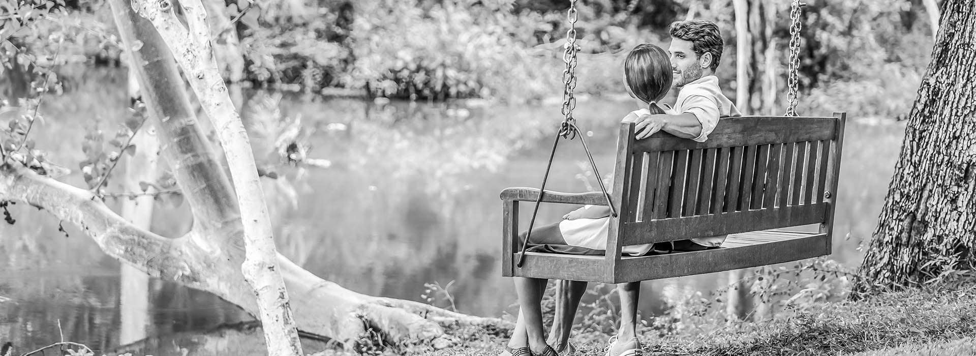 A couple seated on a swing by a lake
